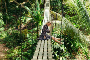 smiling attractive woman sitting on wooden footbridge in jungle
