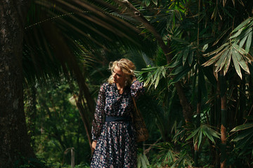 attractive woman in dress standing near trees in jungle