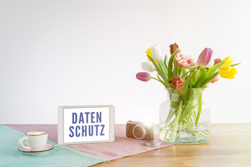 Tablet with Datenschutz writing in german meaning data privacy in english on wooden desk with white background