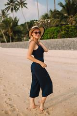 smiling attractive woman in hat standing on sandy ocean beach