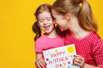 concept of mother's day. mom and child girl with postcard on colored background