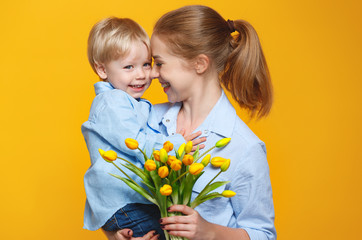 concept of mother's day. mom and baby son with flower on colored background.