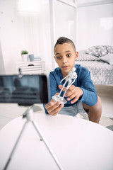 Toy in detail. Clever afro american boy blogger recording video while carrying toy