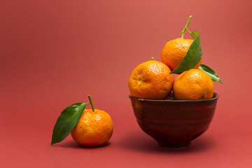 Still life studio shot of a red ceramic bowl with black texture filled with fresh orange tangerines on red background.