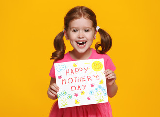 concept of mother's day. cheerful laughing child girl with postcard on colored background