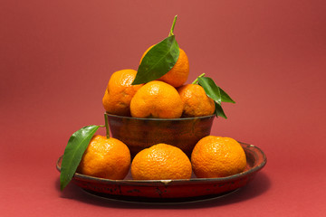 Still life studio shot of a red ceramic bowl and plate with black texture filled with fresh orange tangerines on red background.