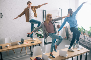 high angle view of happy multiethnic business colleagues dancing on tables in modern office
