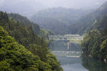 Fukushima , JAPAN - June 19 : The local train Tadami line and Tadami river on June 18 , 2017 in Fukushima , Japan. This train services in East Japan railway company's Tadami line.