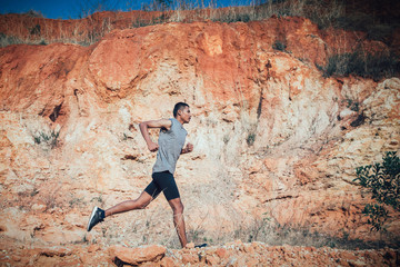 fit man running outdoor cross-country concept of exercising