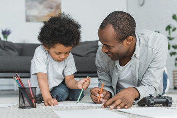 african american father drawing with son on floor at home