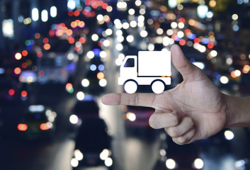 Truck delivery icon on finger over blur colorful night light city with cars, Transportation business concept