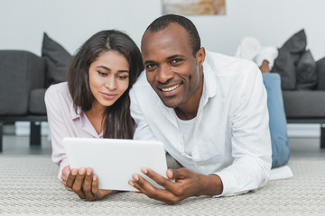 african american girlfriend and boyfriend lying on floor and using tablet at home