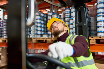 Portrait of young warehouse worker sitting inside forklift moving goods from tall storage shelves and looking up, copy space