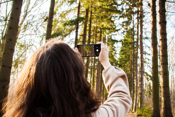 Hands taking pictures of green forest. Picture from behind of the model