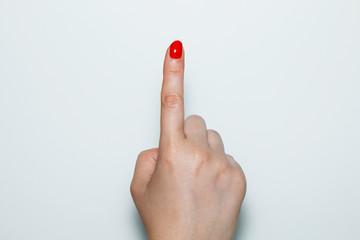 Female hand showing index finger up on white background