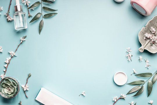 Facial cosmetic products, leaves and cherry blossom on blue table