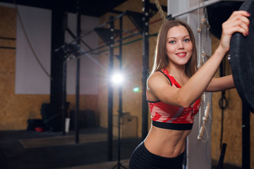 Photo of smiling sportswoman with barbell