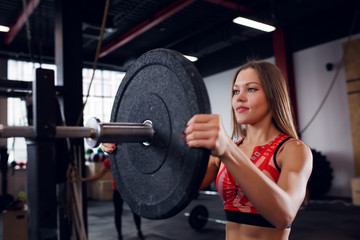 Image of athlete girl in sports clothes with barbell