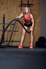 Image of sports woman exercising with two ropes