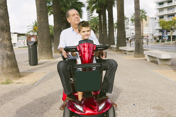 Grandfather and grandson with a electric wheelchair