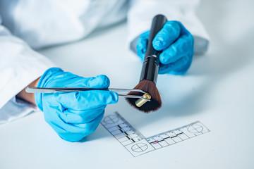 Forensic scientist examining bullet casing