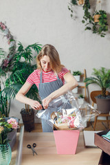 Photo of female florist with stapler decorating floral composition at table with flowers, boxes