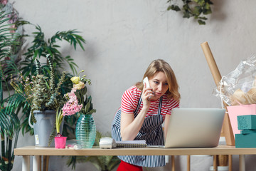 Picture of florist girl talking on phone while sitting at table with computer