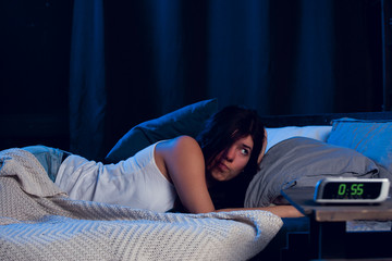 Photo, young brunette with insomnia lying on the bed next to clock