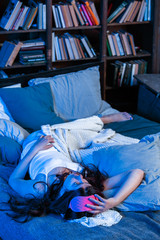 Picture of brunette with insomnia with pink eye bandage lying on bed