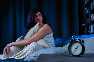 Picture of dissatisfied woman with insomnia sitting on bed next to alarm clock