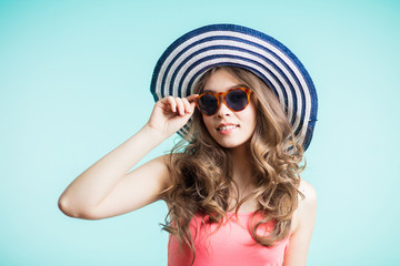 Beautiful girl in a summer hat smiling on blue background