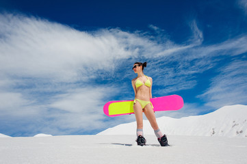 Sexy slim woman with a snowboard against the sky