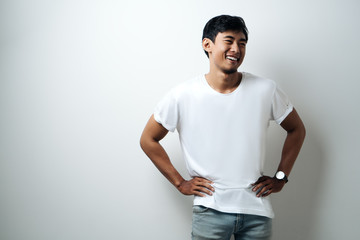 Young asian guy in white blank t-shirt, empty wall, studio portrait