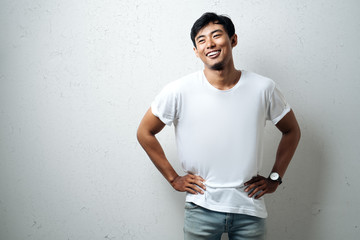 Young asian guy in white blank t-shirt, grunge wall, studio portrait Wall mural