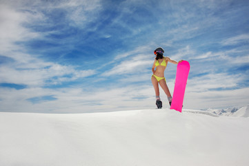 Sexy woman in swimsuit and helmet with a snowboard on the mountain slope