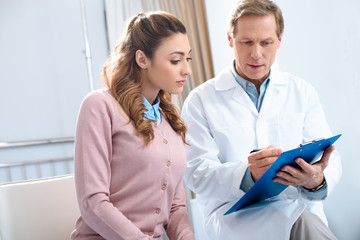 doctor showing something to patient in clipboard in clinic