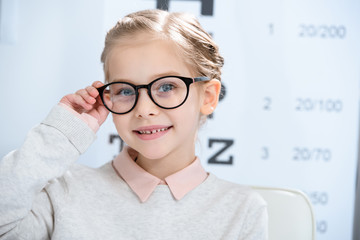 adorable smiling child looking at camera in glasses at oculist consulting room Wall mural