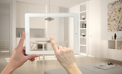 Hands holding and pointing on tablet showing blurry modern kitchen. Real finished minimalist white kitchen in the background, architecture interior design presentation