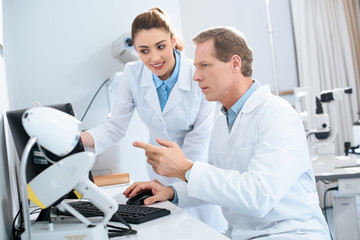 two opticians working with computer in clinic