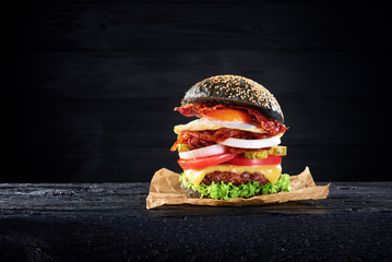 Wall Mural - Black burger with egg and bacon on the wooden table