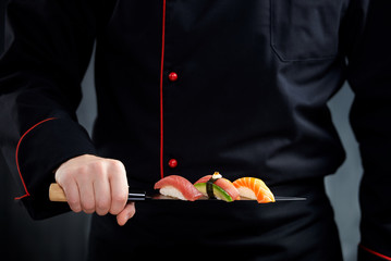 Sushi served on japanese knife in chef hand