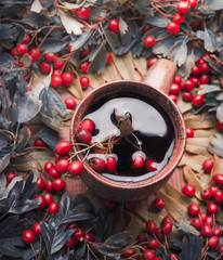 Cup of herbal autumn tea with red berries, top view