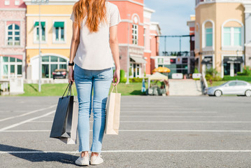 Happy young Asian woman shopping an outdoor market with a background of pastel buildings and blue sky. Young woman smile with a colorful bag in her hand. Outdoor shopping concept.