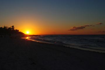 Sunset on the beach in Cuba. Orange sun on the horizon.