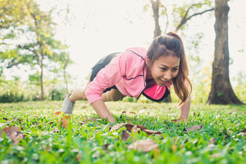 Asian young woman warm up her body by push up to build up her strength before morning jogging exercise and yoga on the grass under the warm light sunshine in the morning. Exercise outdoor concept.