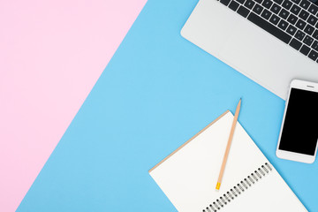 Office desk working space - Flat lay top view mockup photo of working space with laptop, mock up smartphone and blank notebook on pastel background. Blue pink color background working desk concept.