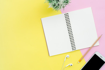 Creative flat lay photo of workspace desk. Top view office desk with notebooks, plant, mock up phone, earphone and copy space on pastel color background. Top view with copy space, flat lay photography