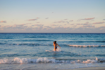 The girl in bikini runs into the sea during sunset. The woman runs into the waves.