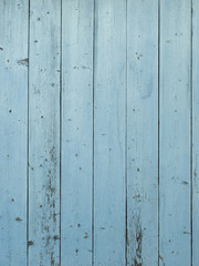 Barn wood wall with distressed, peeling blue paint