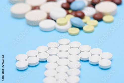 white pills in the shape of an arrow and stack of tablets on
